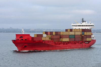 red cargo container ship sailing at sea